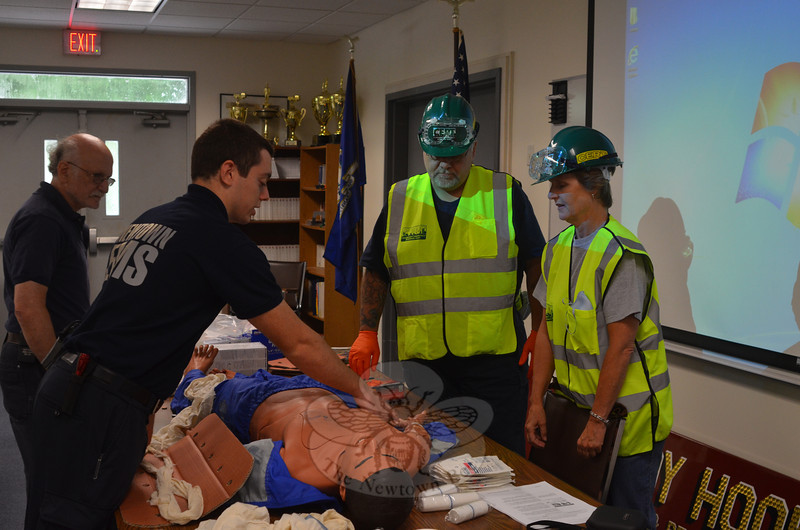Newtown Ambulance Corps volunteers Jordan Reed (in foreground) and Ken Lerman pro-vide Newtown Community Emergency Response Team (CERT) members Karl Sieling and Sarah Cox with some hands-on first aid training during graduation exercises at the Sandy Hook Fire & Rescue headquarters August 11. (Voket photo)
