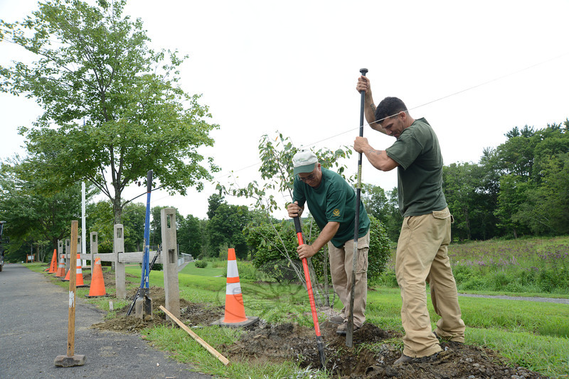 Amandio DosSantos, left, and Nelson Lopes install concrete fencing at Liberty Field. They are replacing wooden fencing and reusing materials from Oakview Field. (Bobowick photo)