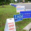A long line of campaign signs stretches the length of Reed Intermediate School's driveway Tuesday during the primary vote in Newtown. (Bobowick photo)