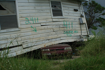 A house sits on an automobile in the lower ninth ward.