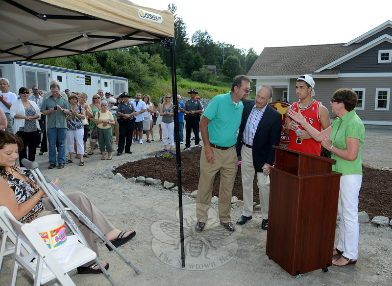 Canine Advocate of Newtown President Virginia Jess, right praises the late veterinarian Brian J. Silverlieb, who spent years caring for animals at the Newtown pound. The new facility is named in his honor. Ms Jess welcomed his brothers Frank Longo, left, Richard Silverlieb, and Dr Silverlieb's son Darryl to the podium.  (Bobowick photo)