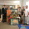 "A group of Middle Gate Elementary School students and parents recently made time to say Thank You to a someone who stepped in to make sure the school's fish continue to have a safe home. Standing from left are parent volunteer Chris Stites, Principal Christopher Geissler, art teacher Jean Walter, parent volunteer Meri Rosenthal, and Donna and Don Bates. The Bateses recently donated a 75-gallon aquarium to the school, replacing a larger one that had been in use for about 20 years. Mr Stites and Mrs Rosenthal are the parent volunteers who have been caring for the fish this past school year. On June 19, parents, faculty, and students gathered in the library to formally thank Mr and Mrs Bates for what Mrs Rosenthal called ""a very generous thing."" Middle Gate students had created a piece of art for the Bateses (inset), a framed image of a fish that incorporated more than 350 student thumbprints, according to Ms Walter. Kneeling with the art are, from left, Ben Rosenthal, Fisher Stites, and Emi Rosenthal.   (Hicks photo)"