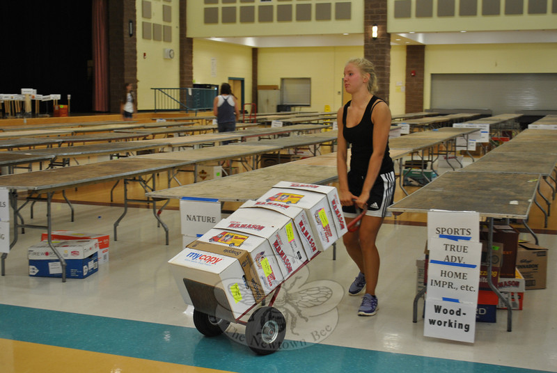 Volunteers with the Friends of the C.H. Booth Library began setting up for their annual book sale, scheduled for July 14-18 at Reed Intermediate School cafetorium, on July 5. On Friday, July 6. Amy Martin, a member of the Newtown High School girls' soccer team, tugs a hand truck filled with books to its proper place in the RIS cafetorium. Amy was one of several soccer team members on hand to help move books in preparation for the July 14 to 18 book sale.   (Crevier photo)