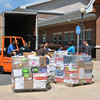 Volunteers with the Friends of the C.H. Booth Library unload a truck full of books outside of the Reed Intermediate School cafetorium, Friday morning, July 6. Setup for the annual book sale, July 14-18, began the previous evening.  (Crevier photo)