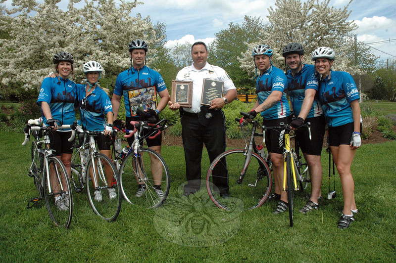 Earlier this month, Newtown Police Lieutenant Christopher Vanghele, center, who is the depart-ment's administrative services commander, accepted honorary plaques from a visiting contingent of Toronto police bicyclists. The plaques state Toronto police's support for Newtown police following the events of 12/14. Nine people from Toronto, including six police and three civilians, made a bicycling stop in Newtown to present the plaques and other gifts to police. Toronto police bicyclists are Sergeant Steve Hicks, Sergeant Andrew Kis, Detective Patrick Meehan, Constable Marcelo Rossi, Constable David Christian, and Constable Juin Pinto. The Toronto civilians are Mary Scholar, Anne Craddock, and Rachelle O'Neil. (Gorosko photo)