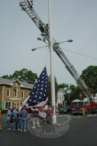 Symbolizing the start of summer in Newtown, on Saturday, May 18, the 600-square-foot summer flag was hoisted up the 100-foot-tall Main Street flagpole, where it will fly through the summer holidays and into the fall.  (Gorosko photo)