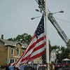 A crew of Newtown Hook & Ladder volunteer firefighters assisted with the rigging required to remove the smaller winter flag from the Main Street flagpole and replace it with the lar-ger summer flag.  (Gorosko photo)
