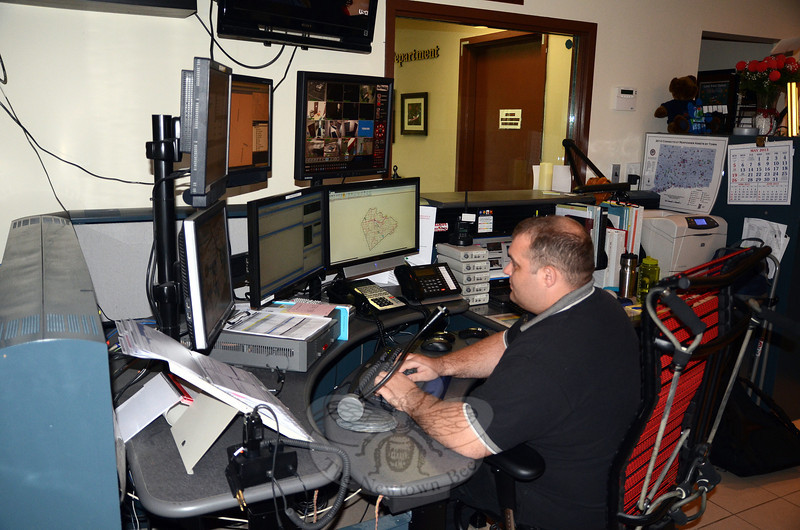 The nine staff members of Newtown's Emergency Communications Center, including Tom Ramsdell, pictured, handle an average of 8,000 calls per year. This is a low enough call volume to justify merging dispatch responsibilities into a regionalized center, according to Maureen Will, who manages the center and its personnel.  (Voket photo)