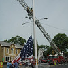 A crew of Newtown Hook & Ladder volunteer firefighters assisted with the rigging required to remove the smaller winter flag from the Main Street flagpole and replace it with the larger summer flag.  (Gorosko photo)
