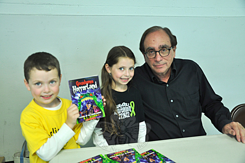 "Nathaniel Hoag, 5, and Jillian Hoag, 6, pose with Goosebumps author R.L. Stine during a meet and greet in the Newtown Middle School cafeteria for the ""Turning the Page, New Stories for Newtown"" event on Saturday, May 18. (Dietter photo)"