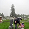 Vietnam War veteran Jake Chapdelaine replaces a flag placed last year with a new American flag, Wednesday morning, May 22, in the Newtown Village Cemetery. Members of VFW Post 308 spread out Wednesday to decorate the gravesites of war veterans in each of Newtown's cemeteries with nearly 1,300 flags, in preparation for Memorial Day, Monday, May 27. Every year the VFW purchases the flags, which remain in place the entire year. (Crevier photo)