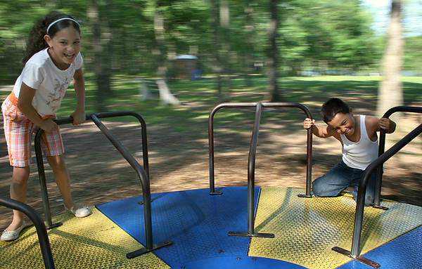 BLAINE FALKENA/Hazleton Standard-Speaker<br /> Samantha Brea, left, giggles as Jonathan Majia climbs onto the merry-go-round at the Hazle Township Community Park after giving it a good spin Wednesday afternoon July 2nd, 2008.