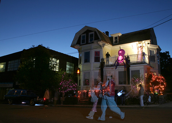 BLAINE FALKENA/Hazleton Standard-Speaker<br /> Trick-or-treaters visit a house on the corner of Vine and Green Streets Wednesday night, October 31, 2007 as others make a ghostly apparition as they walk back across the street.