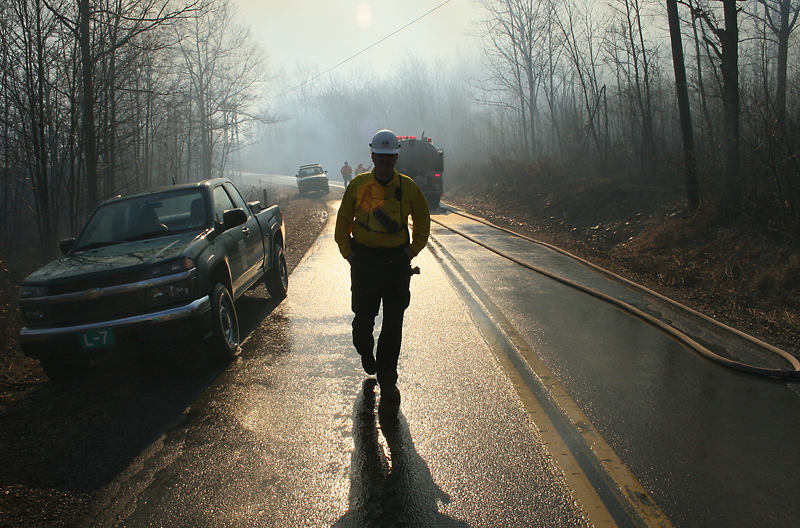 BLAINE FALKENA/Hazleton Standard-Speaker<br /> Charles Engel of DCNR walks down Tunnel Road after spray from an air tanker soaked the area while fighting a brush fire Monday afternoon, March 23rd, 2009.