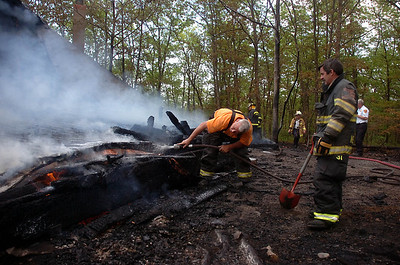 5/25/11 Westwood- Firefighters place their hose underneath a collapsed portion of roof that was on a recreation hall building that caught fire at Camp Grossman on Hale Reservation property in Westwood Wednesday afternoon. Photo by Sean Browne, Westwood Press