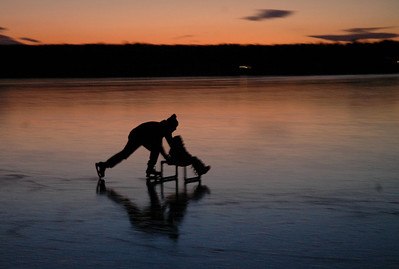 12/20/05 Sharon- Ross Solomon pushes his 5 and a half year-old daughter around as the sunsets over Lake Massapoag Tuesday evening.  Photo by Sean Browne, Sharon Advocate