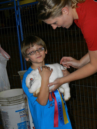 Volunteer Julia Bell helps Oklahoma School for the Blind student Jimmy Anderson hold a rabbit at OSB's Western Heritage Day.