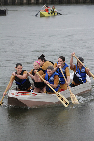 The Pottawatomie Nation boat and its crew paddle across Three Forks Harbor in the River Rumba Regatta.