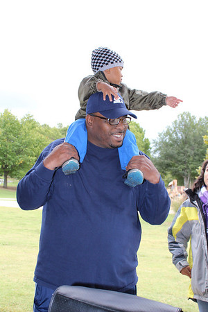 Marques Smith sits on his father's shoulders as they watch the Muskogee High School choir perform at Animalfest. Special photo by Travis Sloat