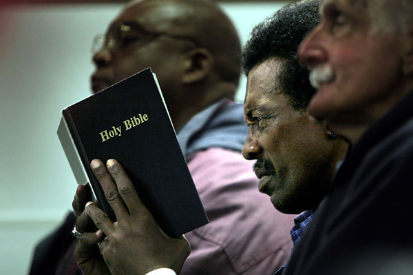 A parishioner strains to read some Bible passages during nightly chapel and prayer services at the Bay Area Rescue Mission in Richmond, California.