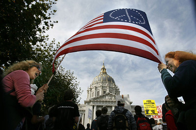 Diane Perea of Nevada City, Calif.  and Mindy Oberne of Grass Valley, Calif. raise a peace flag, framing the City Hall, during an anti-war rally at Civic Center, Saturday, Oct.27, 2007 in San Francisco.  (AP Photo/Dino Vournas)