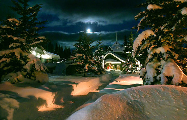 A full winter moon appears out of a clearing sky in Lake Louise, Alberta, Canada.