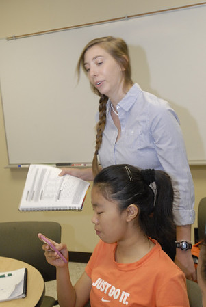 Fiona Zhang, 12, checks her smart phone while English immersion teacher Elaina Ross looks over her shoulder.