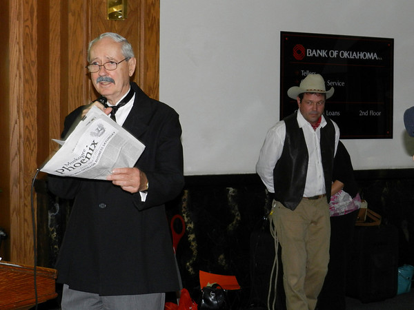 """Tams Bixby,"" who purchased the Muskogee Phoenix in 1906, gives a speech during the Severs Hotel gala, as ""Will Rogers"" waits in the background."