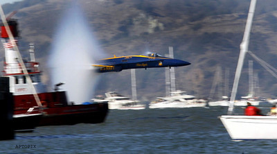 One of the Blue Angels makes a high-speed pass, sending a water vapor cloud radiating from the F-18 fighter, as the precision flying team highlighted an air show as part of Fleet Week in the San Francisco Bay Area, Sunday, Oct. 7, 2007.  (AP Photo/Dino Vournas)