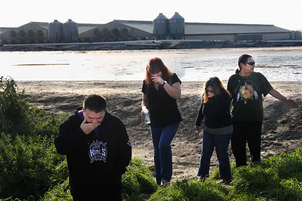 Residents of Briggs Road, Wayne Yepez, Janice Magaoay and Yepez's parents, Lynda and Larry, react to the stench from a lake of chicken excrement, background, at the Olivera Egg Ranch, that residents blame for their health problems, Wednesday, Feb. 17, 2010 in Lathrop, Calif.  AP Photo/Dino Vournas