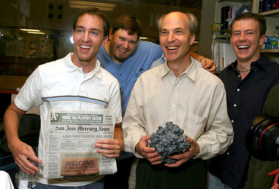 Stanford University professor Roger Kornberg, second from right, holds a model of a protein machine and jokes around with his staff, celebrating his Nobel Prize in Chemistry for his work in the field of gene expression at Stanford, California, October 4, 2006.   The newspaper headline is from the previous announcement of a Nobel win by another Stanford professor.  REUTERS/Dino Vournas (UNITED STATES)