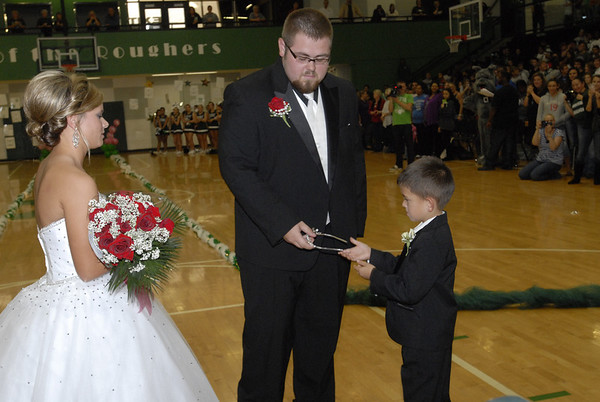 Muskogee High School senior J.B. Clark takes a crown from Carson Coleman as he prepares to crown 2012 Homecoming Queen Hannah Alexander. The coronation was held Friday during a raucous pep rally.