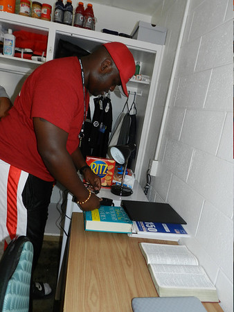 With his Bible on the table opened to the 23rd Psalm, Bacone College freshman Ishmael Barnett of Houston, plugs things into his dorm room wall. Football players moved into their rooms Tuesday while other students move in through early next week.
