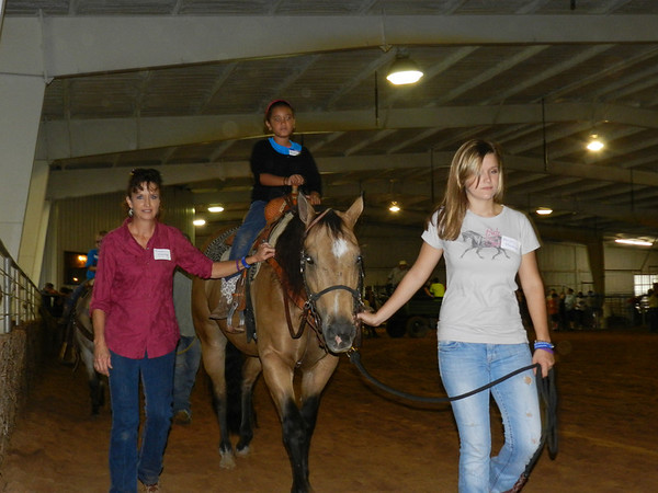 Volunteer Maggie Hackler, left, walks with 8-year-old Oklahoma School for the Blind student Sarah Moyer as Hayley Hackler leads a horse around the ring during OSB's Western Heritage Day.
