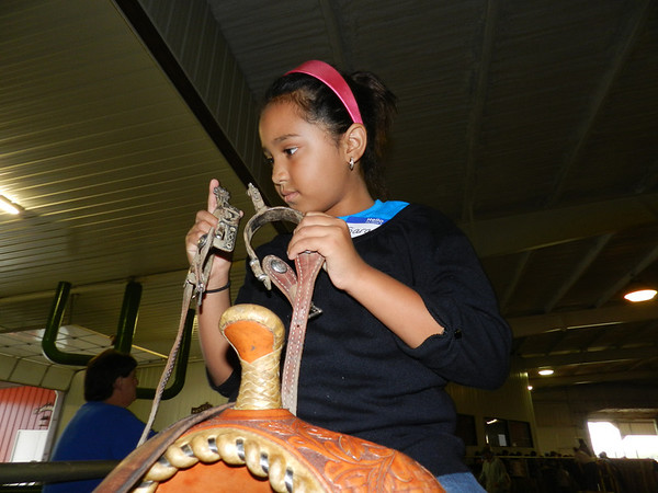 """Oklahoma School for the Blind student Sarah Moyer, 8, of Woodward, feels a pair of spurs while riding a horse at OSB's Western Heritage Day. During her indoor """"trail ride,"""" Sarah got to feel a stirrup, horseshoe, chaps and other equestrian gear."""