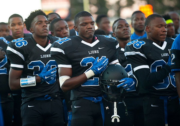 The John Tyler High School's Nicholas Thompson (26), Da'Qualyon Kennedy (21) and Michael Washington (88) observe the playing of the Star Spangled Banner before the start of their game Friday night against rival Robert E. Lee at Trinity Mother Frances Rose Stadium.  (Sarah A. Miller/Tyler Morning Telegraph)