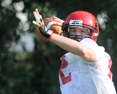Lee QB Raleigh Poster throws in a passing drill at the Red Raiders  first practice Monday morning. Herb Nygren Jr 081312