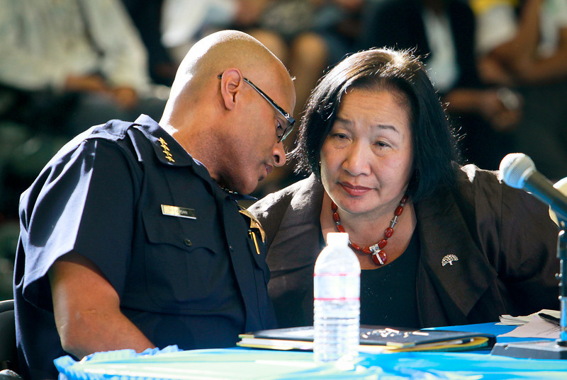 Oakland Mayor Jean Quan has a word with interim Police Chief Howard Jordan during the presentation of a new crime prevention plan at Laney College in Oakland, Calif., on Thursday, October 15, 2011.