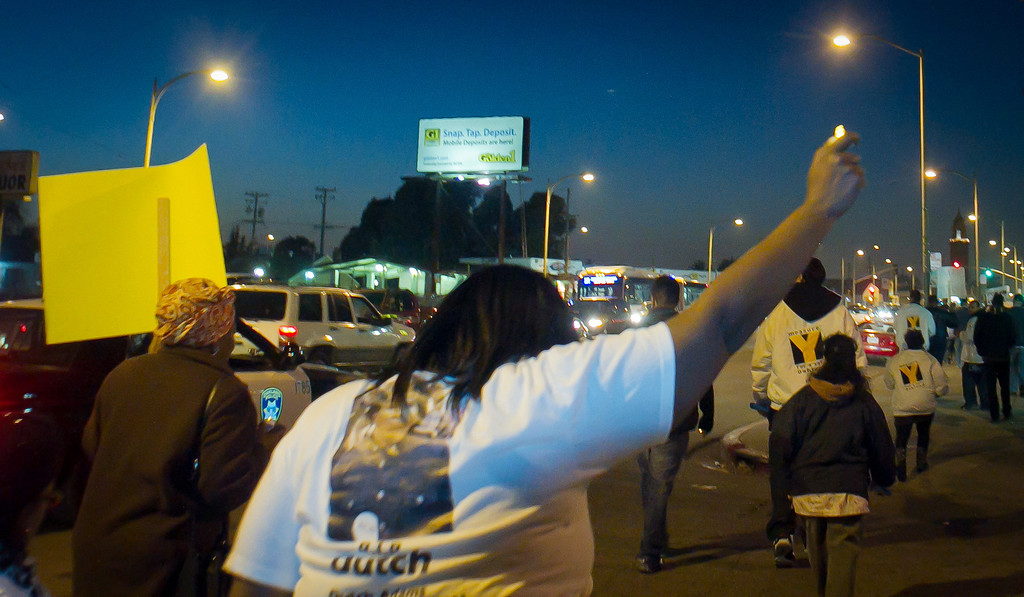 People march down International Blvd. during the a Peace Walk for those harmed by gun violence in Oakland, Calif., on Friday, December 9th,  2011.