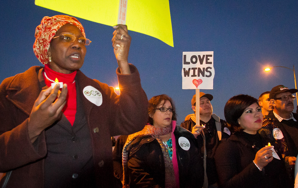 Francine Peters holds a sign during the memorial & peace walk for those harmed by gun violence in Oakland, Calif., on Friday, December 9th,  2011.