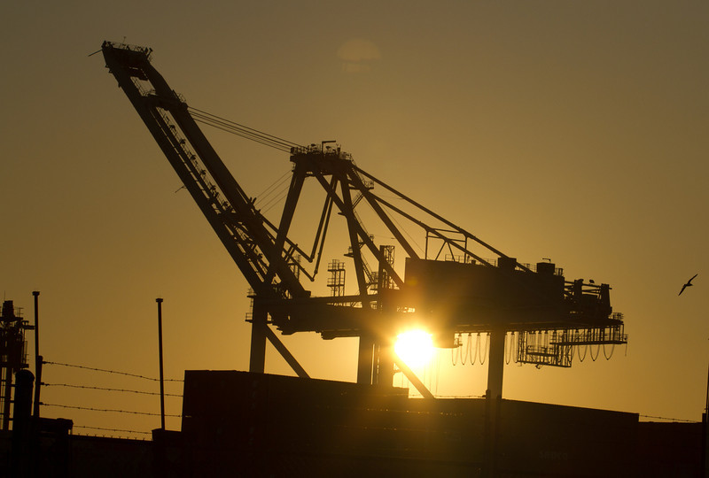 The sun sets behind an idle crane in the Port of Oakland in Oakland, Calif., on Friday, December 9, 2011. Story about how Occupy Oaklland plans to shut down the port on December 12th.