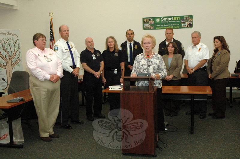 Flanked by town officials at Newtown Municipal Center on October 10, First Selectman Pat Llodra announced the town's participation in the Smart 911 emergency telephone system. The Smart 911 system allows its callers to automatically provide pertinent detailed information to emergency dispatchers when the 911 callers place an emergency call. Shown, from left, are Emergency Communications Director Maureen Will, Police Chief Michael Kehoe, Newtown Volunteer Ambulance Corps Officer Mike Collins, Newtown Volunteer Ambulance Corps Assistant Chief Sharon McCarthy, Police Captain Joe Rios, Police Lieutenant George Sinko, Public Health Director Donna Culbert, Emergency Management Director Bill Halstead, and Town Clerk Debbie Aurelia. (Gorosko photo)