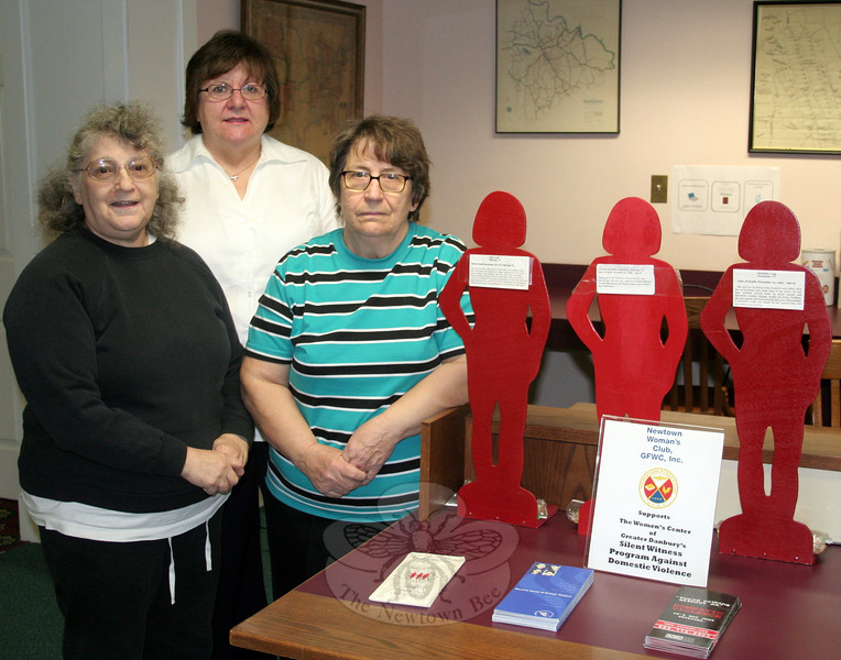 Newtown Woman's Club members, from left, Betty Warner, Nina Morrison, and Marion Thompson are hoping that visitors to C.H. Booth Library this month will take a few minutes to recognize three local victims of domestic violence honored in a small display on view in the main lobby. Others may benefit from the information left by the club during this, Domestic Violence Awareness Month.(Hicks photo)