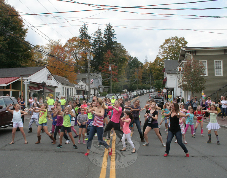 """Dancers from The Graceful Planet turned a small section of Church Hill Road into a performance space for a few minutes on Saturday, October 6, when they assembled and danced to """"Gangnam Style."""" The dancers had a built-in audience, considering a few hundred people were in Sandy Hook Center that afternoon for the 2nd Annual Passport To Sandy Hook, a special event that encouraged people to walk around and explore the district while taking a chance on three prizes that had been created from donations by the businesses within the area. (Hicks photo)"""