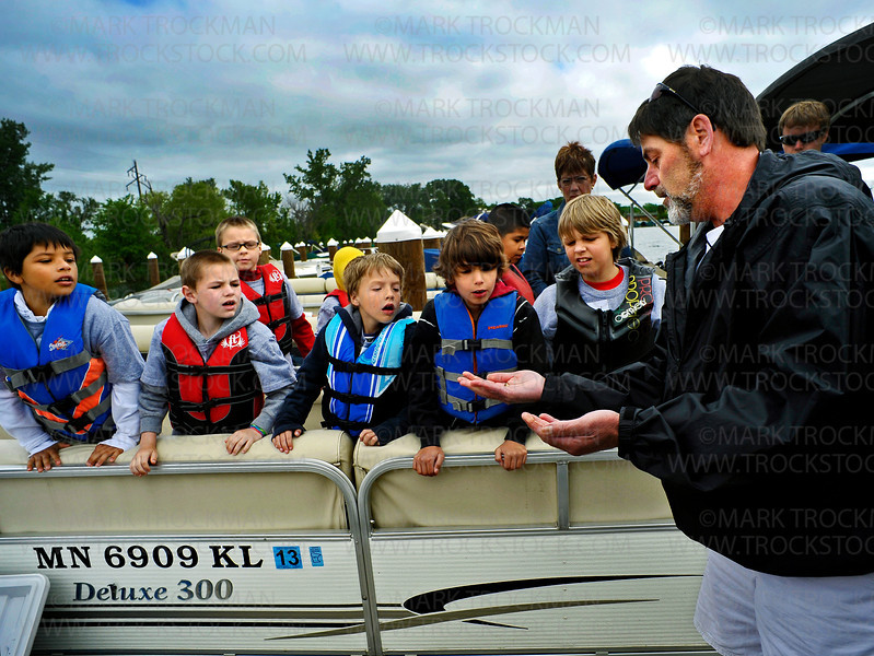 Boys from the Hopkins School District get a hands-on demonstration showing the types of fish bait available to them and how to put each type on a hook by Al Stein Thursday, June 9, aboard a rental boat at Excel Boat Marina on St. Albans Bay on Lake Minnetonka in Excelsior.  About two dozen Hopkins School District students from under privileged living situations spent the day on the lake during the free Cops and Kids Fishing Event.