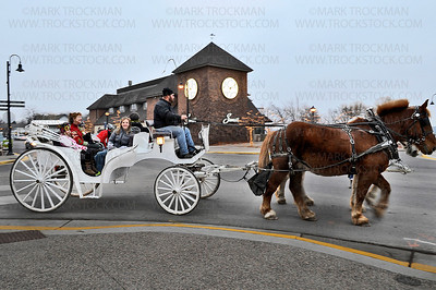 Bayfront Carriages owner Andrew James takes a left from Broadway Ave. S.,  on to Lake St. E., in Wayzata Friday, Nov. 30, guiding his two Bergeron horse's Mick and Barney (obscured behind other horse) to pick up another group people for a free carriage ride Wayzata's holiday kickoff.