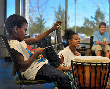 Ebrima Sarge, left, five, and his mother, Kenna Cottman, center, beat a rhythm during 'Global Folk: West African Drum and Dance' program Saturday, Sept. 15, at the Plymouth Library.  Sheila Parviz, right, Plymouth, was one of about 15 participants at this interactive program which included drumming, dancing, rhythm-making, and singing, free of charge.