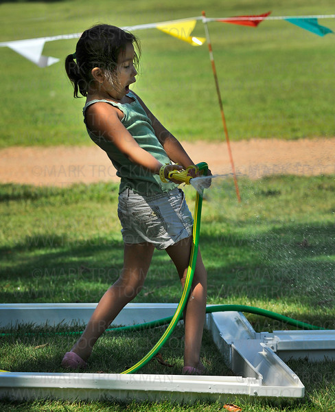 Six year old Delila Ruiz sprays the the duck race apparatus with water on a hot Saturday in Long Lake during the Corn Days festival, put on by the Church of St. George.