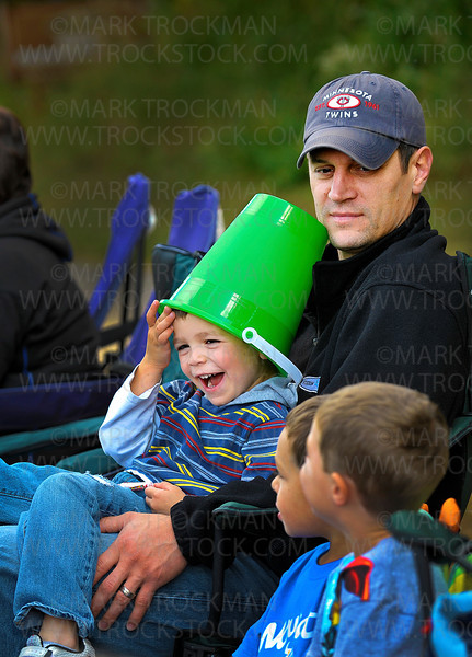 A lime green beach bucket makes a great hat for four-year-old Cooper Theising, New Hope, as he sits on his dad, Nick's lap, along Plymouth Blvd. Saturday, Sept. 24, during Plymouth on Parade.