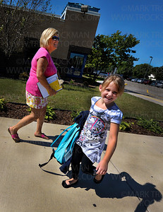 Lily Regensburger, right, is the first PM Kindergarten student to arrive on the first day of classes Wednesday, Sept, 7, at Plymouth Creek Elementary School.  Lily's teacher, Jane Johnson, begins the slow process of gathering her students as they arrive, a few at a time, getting to school with parents and family friends due to a late bus.